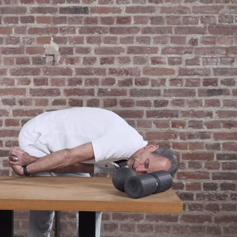 Dehnübung des hinteren Unterarms zur Behandlung eines Tennisellenbogens, bei Roland Liebscher-Bracht seinen Oberkörper parallel zur Tischplatte ablegt und mit dem linken Arm seinen rechten Unterarm an der Hinterseite aufdehnt