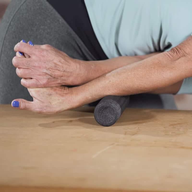 Dehnübung des vorderen Unterarms zur Behandlung eines Tennisellenbogens, bei der die Patientin mit dem linken Arm ihren rechten Unterarm dehnt und diesen dabei bis zur Innenseite des Ellenbogens mit der Mini-Faszienrolle abrollt
