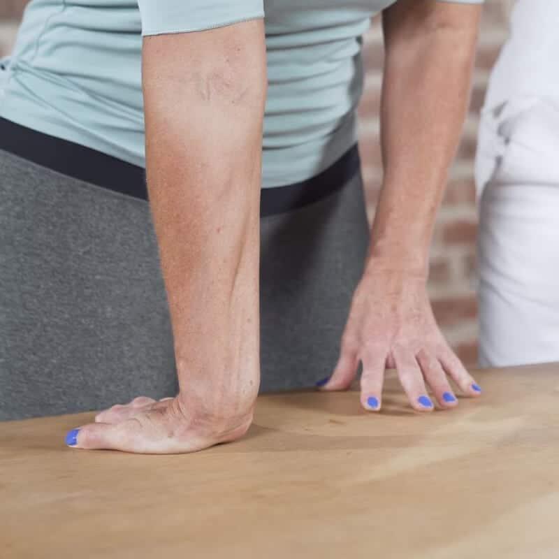 Vorbereitung der Dehnung des vorderen Unterarms zur Behandlung eines Tennisellenbogens, bei der die Patientin an einem Tisch steht und ihr Handgelenk so beugt, dass die Fingerspitzen in Richtung Oberschenkel zeigen,