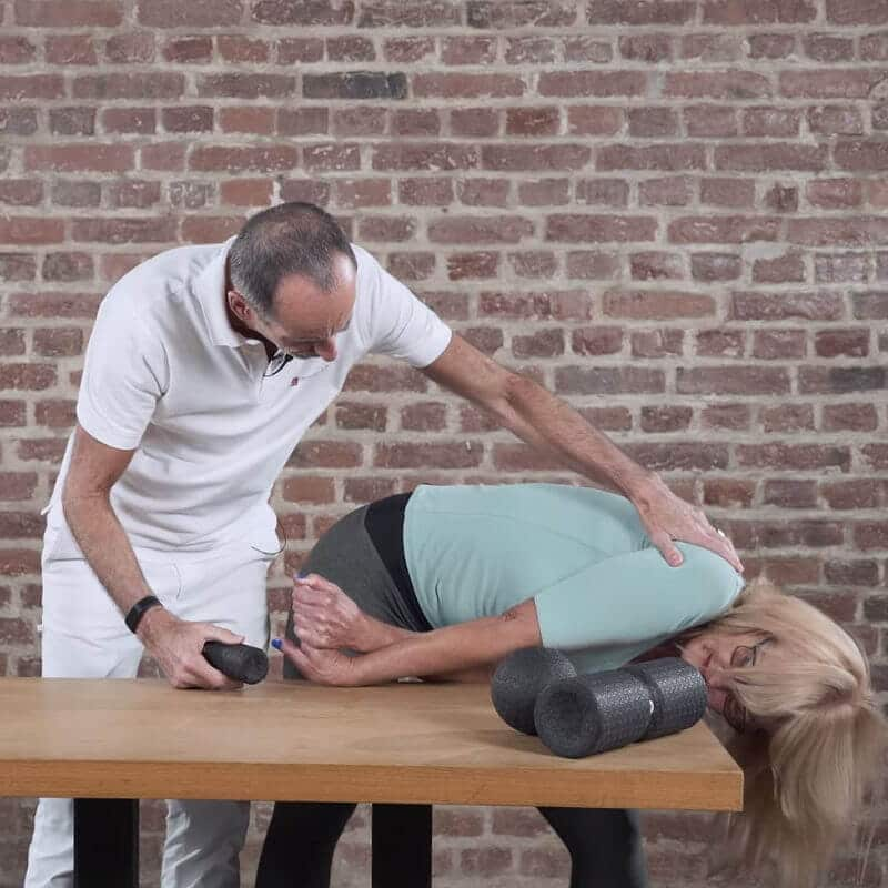 Dehnübung des vorderen Unterarms zur Behandlung eines Tennisellenbogens, bei der die Patientin, angeleitet von Roland Liebscher-Bracht, ihren Oberkörper parallel zur Tischplatte ablegt und mit dem linken Arm ihren rechten Unterarm dehnt