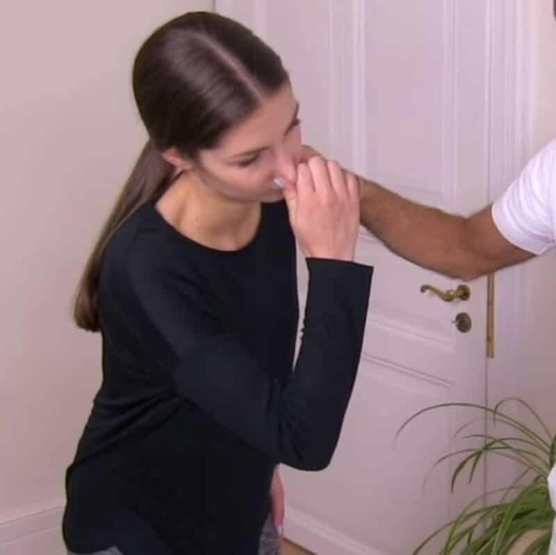 Eine Patienten führt eine Atemübung gegen Interkostalneuralgie durch, wobei sie sich die Nase zuhält