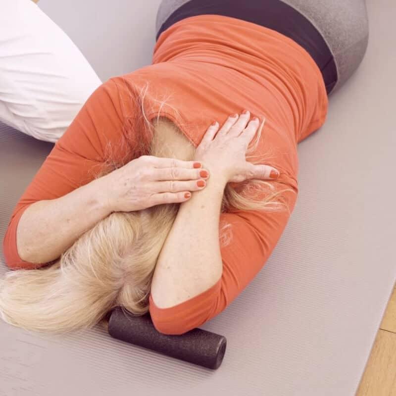 Eine Patientin mit Golferellenbogen dehnt die Beugemuskeln ihres Oberarms