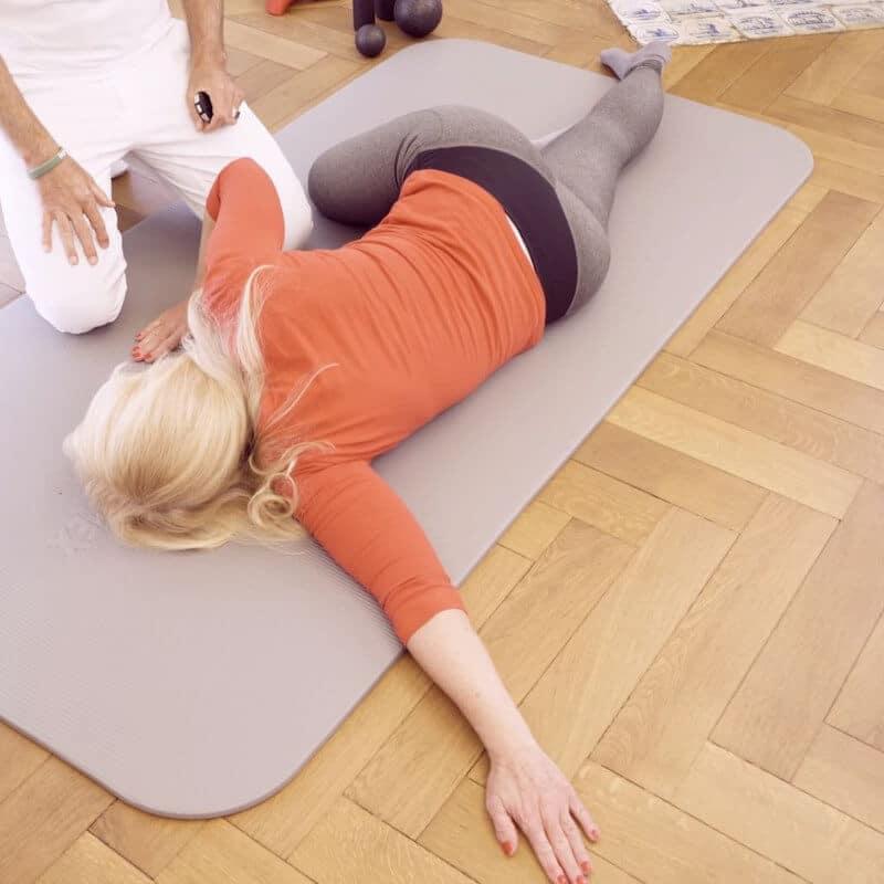 Eine Patientin mit Golferellenbogen dehnt die Streckmuskeln ihres Oberarms