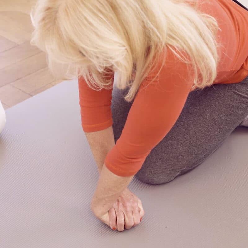Eine Patientin mit Golferellenbogen dehnt die Streckmuskeln ihres Unterarms
