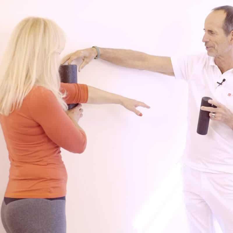 Eine Patientin mit Golferellenbogen rollt ihren hinteren Oberarm an der Wand mit einer Faszienrolle ab