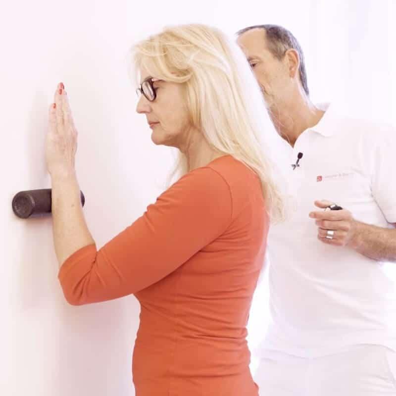 Eine Patientin mit Golferellenbogen rollt ihren vorderen Unterarm an der Wand mit einer Faszienrolle ab
