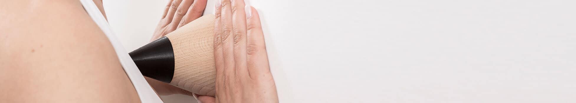 """Zwei Frauenhände halten den """"Drücker"""" mit der flachen Seite an die Wand und mit der Spitze drückt sie sich einen Punkt in Brusthöhe"""