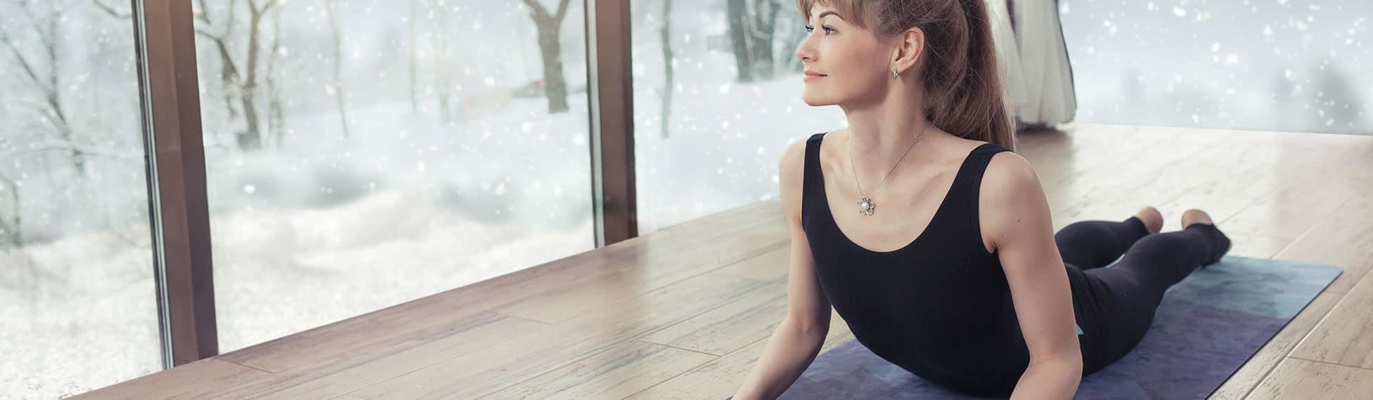 Ein sportliche Frau liegt auf der Matte, geht ins Hohlkreuz und schaut aus dem komplett verglasten Raum heraus auf eine im Schneefall versunkenen Wald