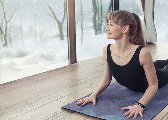Eine junge Frau liegt auf einer blauen Matte und trägt schwarze Kleidung. Im Hintergrund sieht man durchs Fenster Bäume und es schneit.