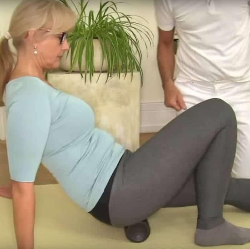 Patientin führt die Faszien-Rollmassage mit der Medi-Rolle gegen ISG-Schmerzen aus