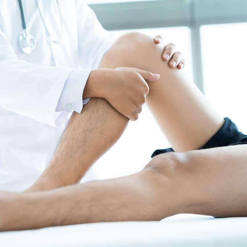 Arzt testet die Beweglichkeit des Patienten, der auf einer Behandlungsliege liegt