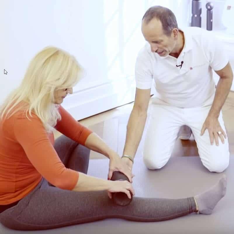 Patientin wendet die Faszienrollmassage an der Vorderseite des Oberschenkels gegen Meniskus-Schmerzen an