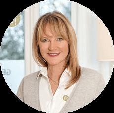 Bild einer lächelnden Frau (Dr. med. Petra Bracht) in einem Kreis von Kopf bis Brust mit weißem Liebscher & Bracht Gesundheitszentrum Shirt und grauer Weste darüber
