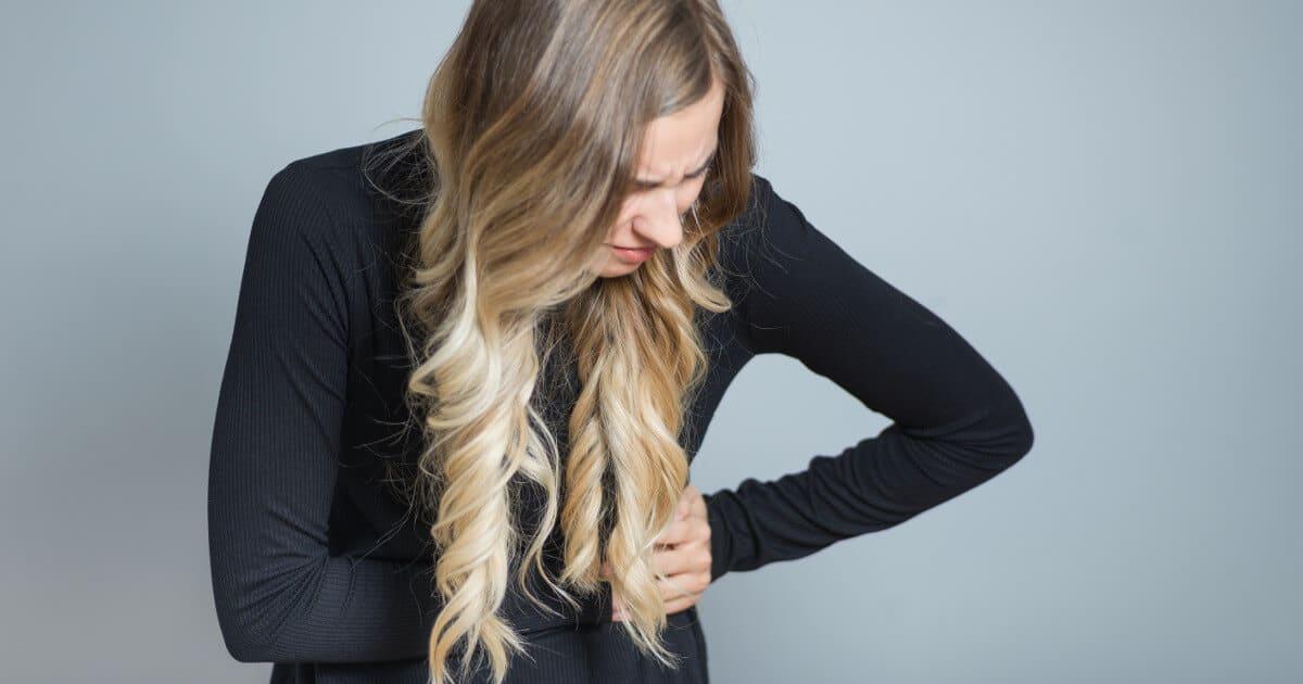 Eine junge Frau hält sich schmerzverzerrt ihre linke Rippengegend