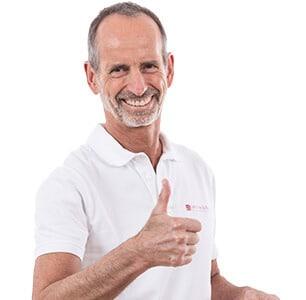 Roland Liebscher-Bracht lächelt glücklich in weiß gekleidet in die Kamera und hat seinen rechten Daumen hoch erhoben vor seiner Brust.