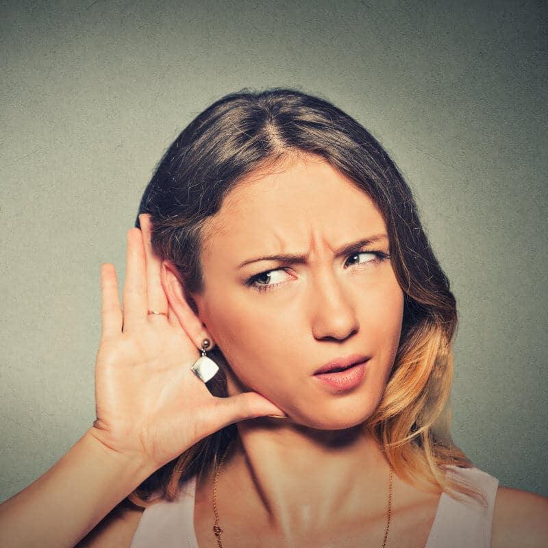 Eine junge Frau hält sich fragend die Hand ans Ohr