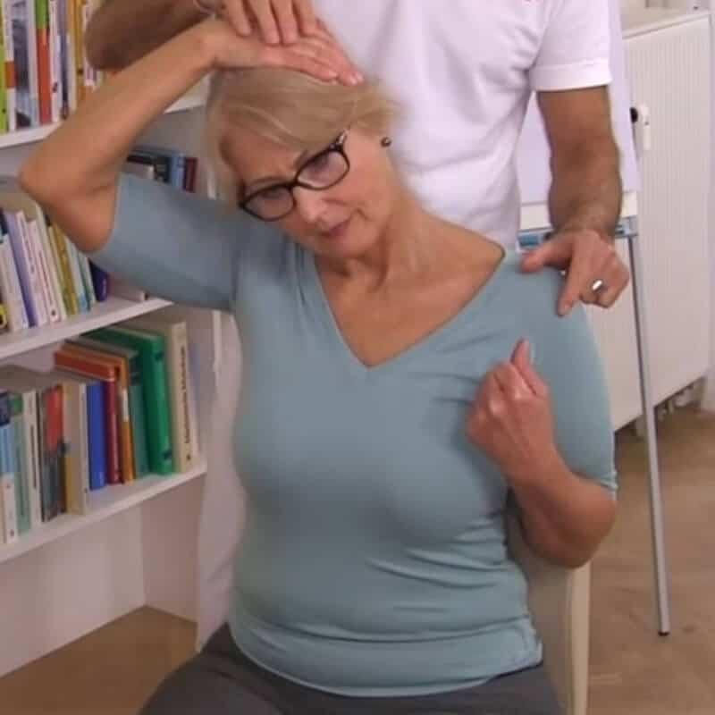 Eine Patientin dehnt ihre Halsmuskulatur zur Behandlung ihres Schiefhalses