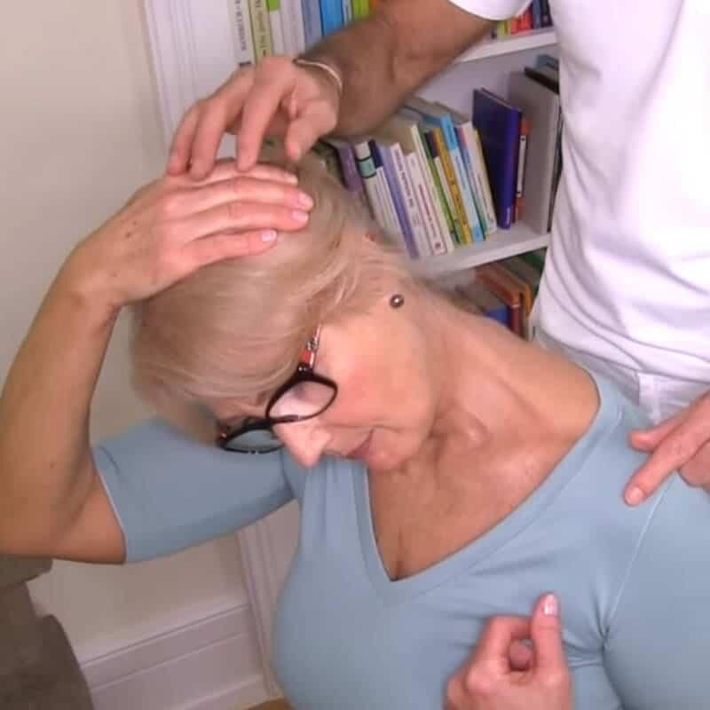 Eine Patientin dehnt ihre schräge Halsmuskulatur zur Behandlung ihres Schiefhalses