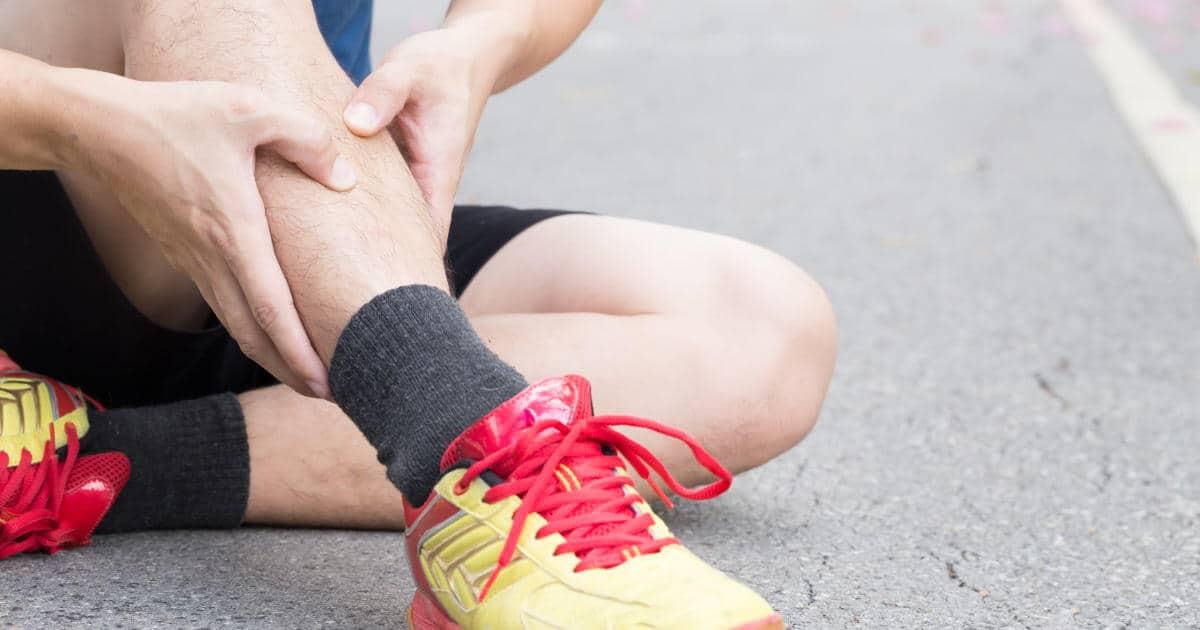 Läufer sitzt auf dem Boden und hält sich sein schmerzendes Schienbein