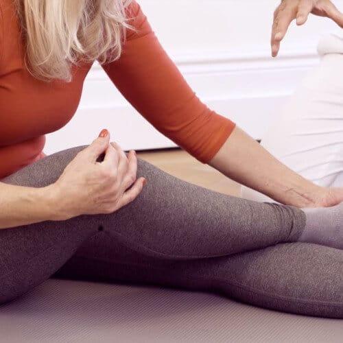 Patientin führt Übung gegen Schienbeinschmerzen im Sitzen aus