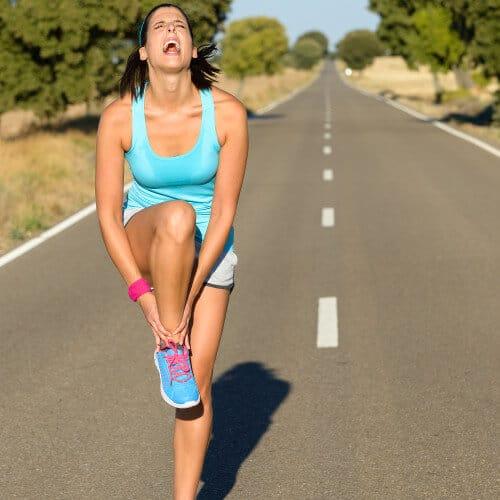 Laeuferin im Training trotz Schmerzen. Sie haelt sich vor Schmerzen den Unterschenkel