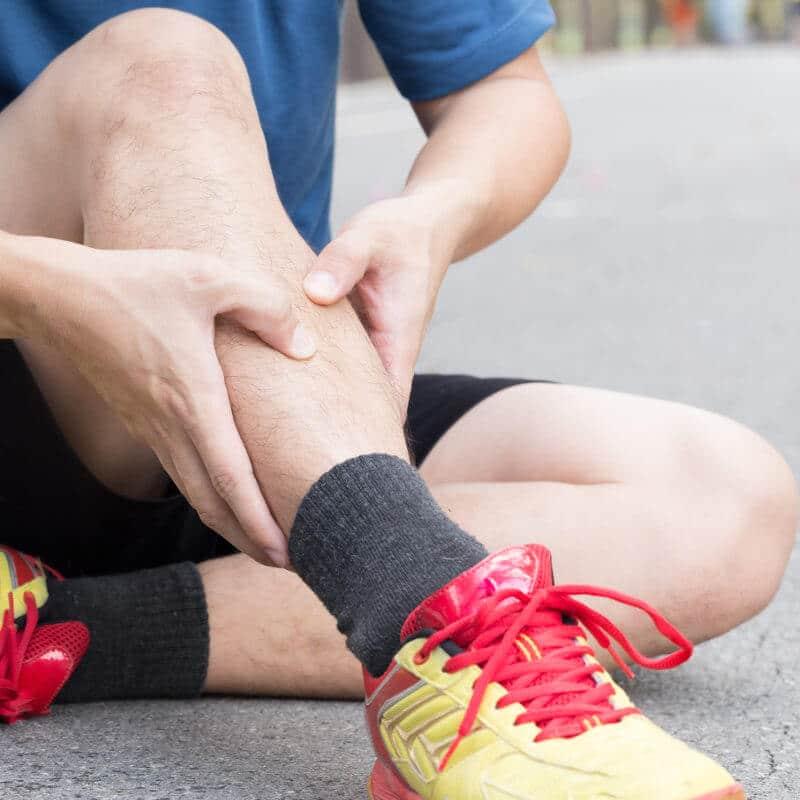 Läufer sitzt auf dem Boden und hält sich vor Schmerzen sein Schienbein
