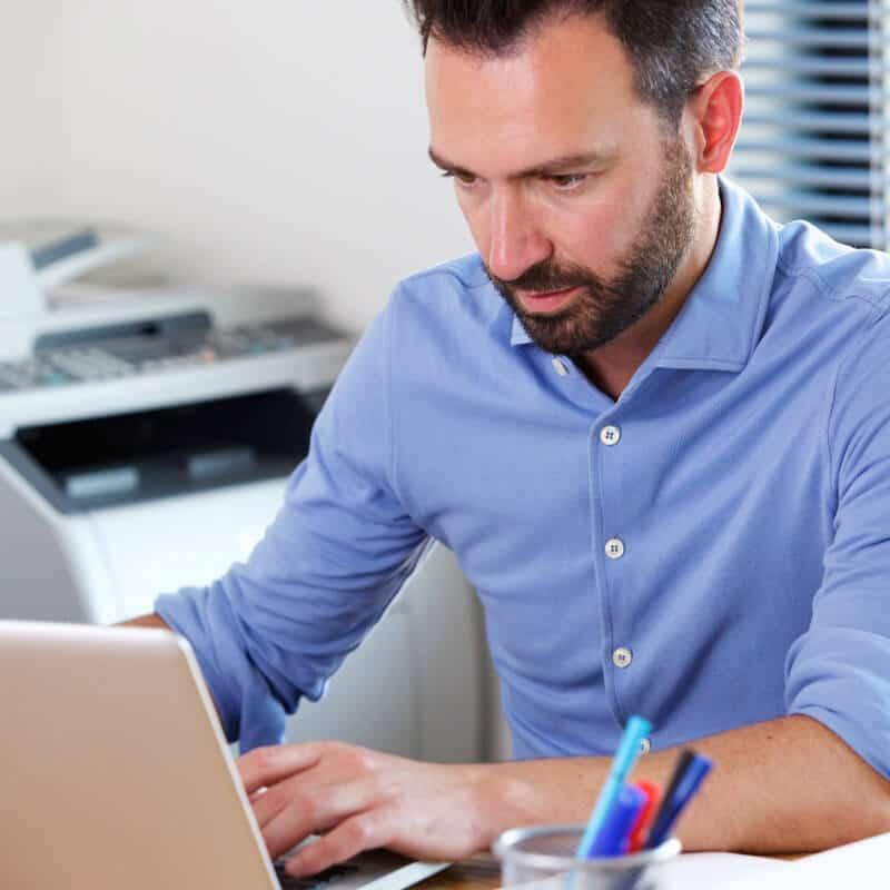 Ein Mann sitzt konzentriert vor seinem Laptop