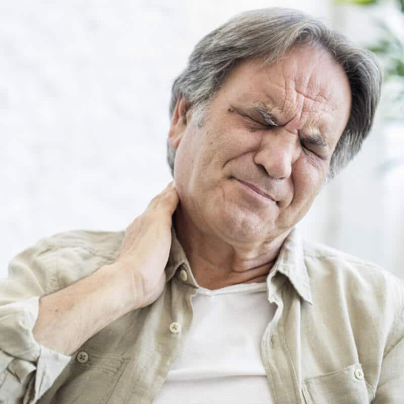 Ein älterer Mann mit Schiefhals hält sich seinen schmerzenden Nacken
