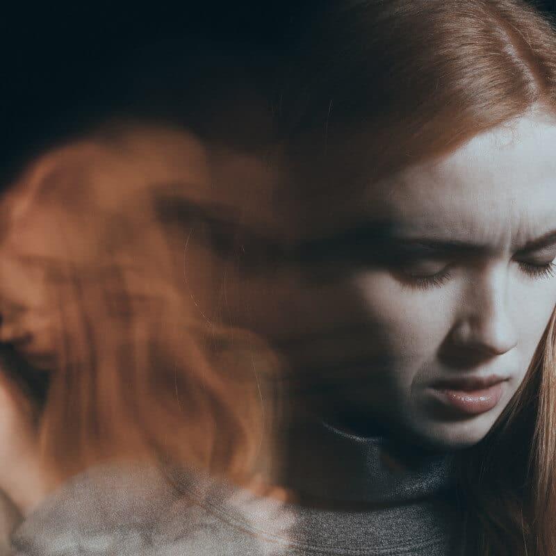 Eine junge Frau vor schwarzem Hintergrund blickt deprimiert nach unten