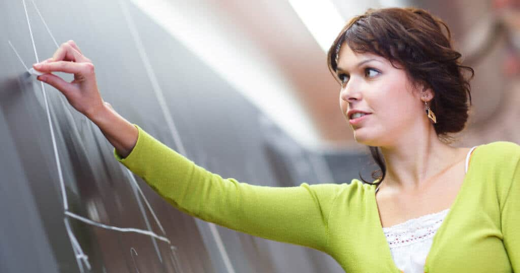 Eine junge Lehrerin zeichnet etwas an die Tafel, ihr Handgelenk ist überstreckt