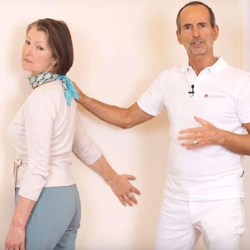 Schmerzspezialist Roland Liebscher-Bracht leitet eine Patienten bei einer Dehnübung gegen Kalkschulter an und zeigt ihr, in welchem Winkel sie ihren rechten Arm an der Wand in der Ausgangsstellung ablegen soll