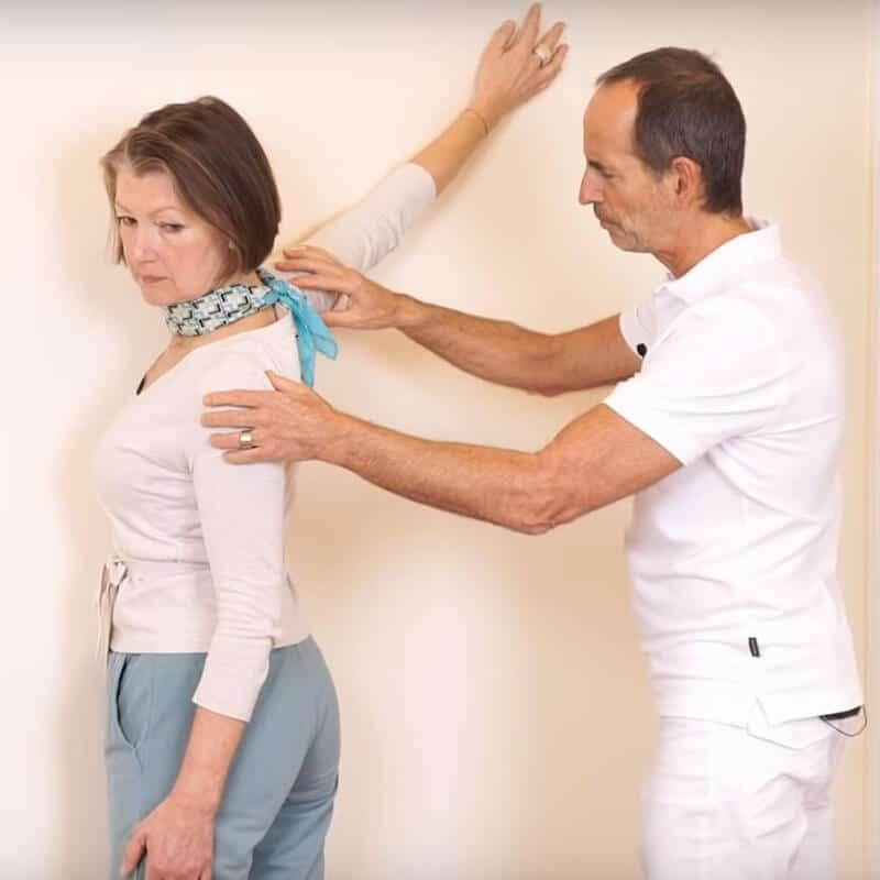 Schmerzspezialist Roland Liebscher-Bracht leitet eine Patienten bei einer Dehnübung gegen Kalkschulter an und zeigt ihr, in welchem Winkel sie ihren rechten an der Wand ablegen soll