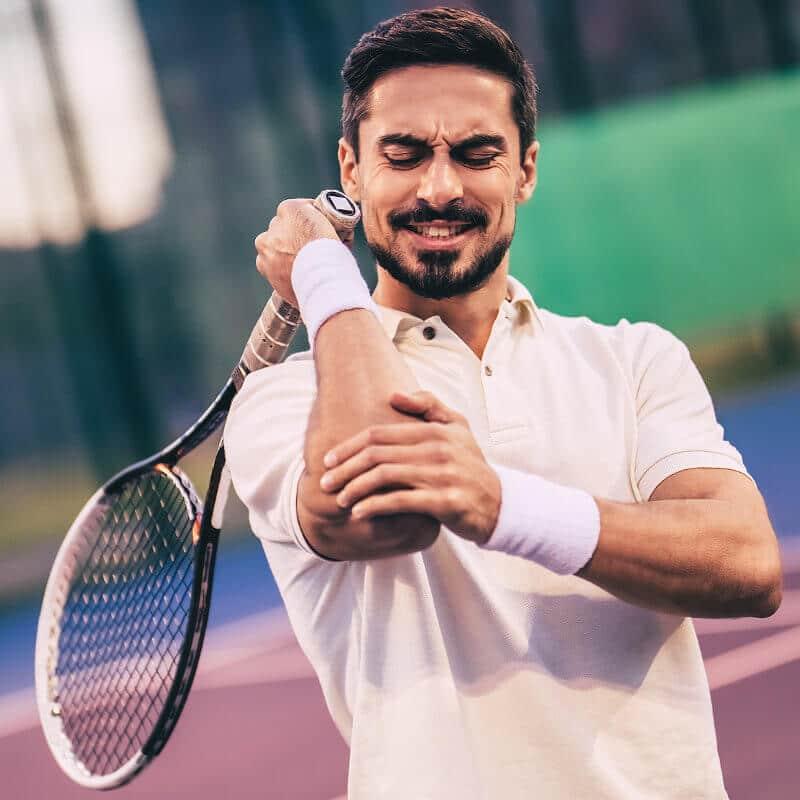 Ein Tennisspieler hält sich seinen schmerzenden Ellenbogen