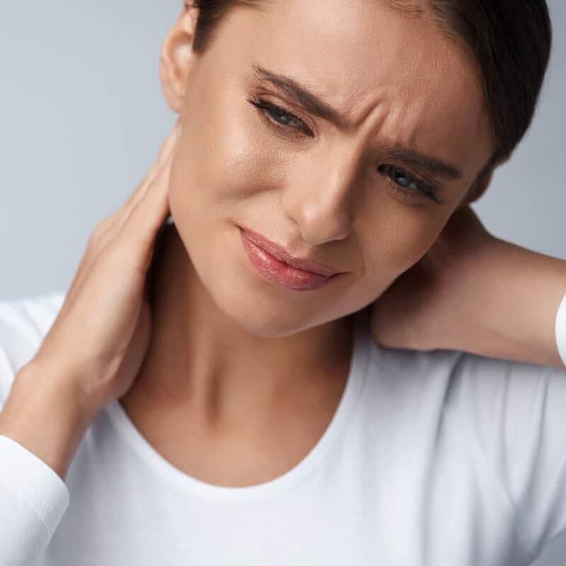 Eine Frau neigt den Hals zu ihrer linken Schulter und hält sich vor Schmerzen ihren Nacken