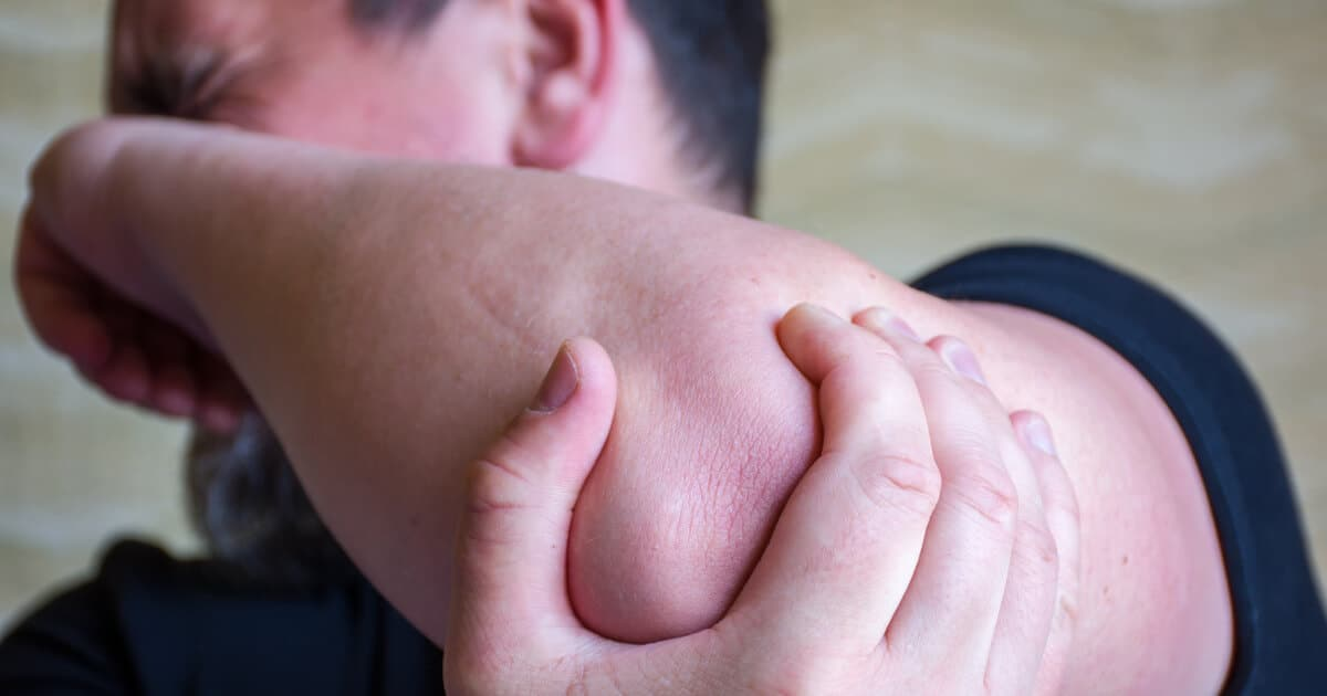Ein Mann hält sich vor Schmerzen seinen Golferellenbogen