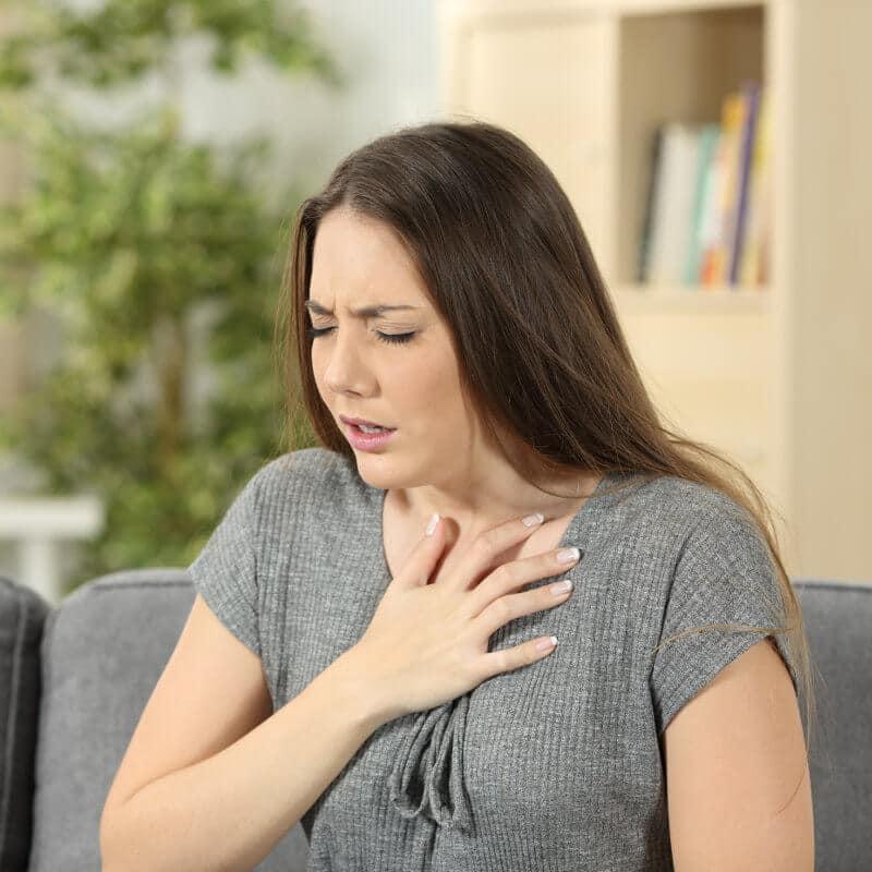 Eine Frau hat Schmerzen beim Atmen und hält ihre Hand auf den Brustkorb