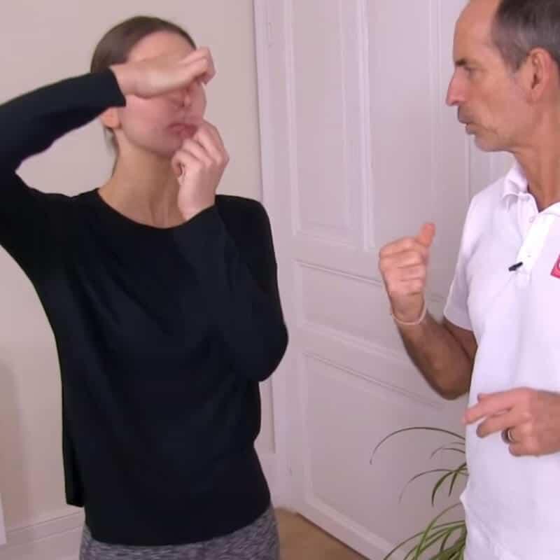 Angeleitet von Roland Liebscher-Bracht hält sich eine Patientin bei der Übung gegen Asthma Mund und Nase zu