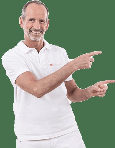 Roland Liebscher-Bracht ist weiß angezogen. Er zeigt mit seinen beiden Händen bzw. Zeigefingern nach rechts und lächelt.