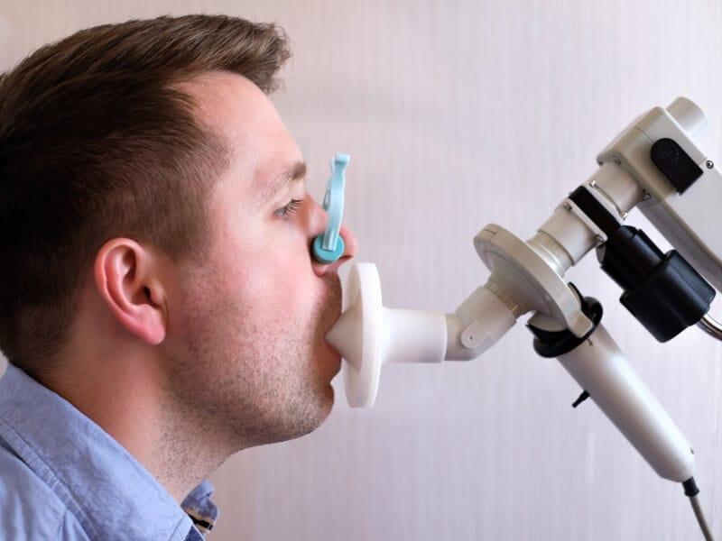 Mann sitzt am Spirometer für einen Lungenfunktionstest