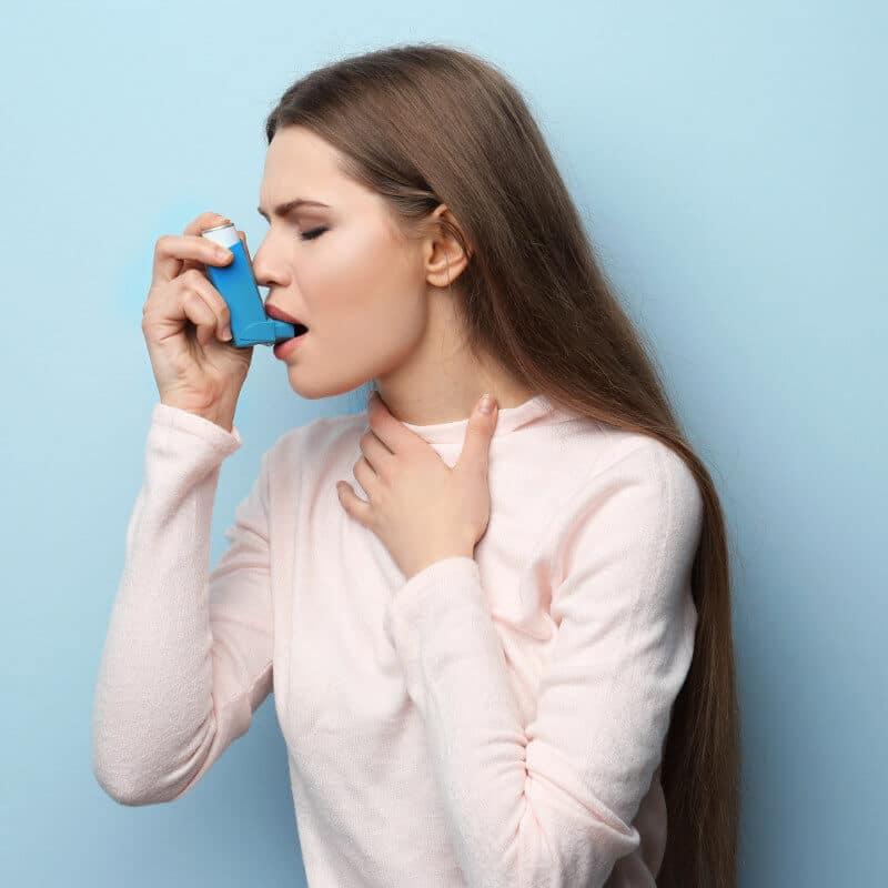 Frau benutzt einen Inhalator gegen Asthma