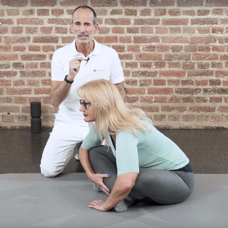 Patientin führt im Sitzen mit angewinkelten Knien und überkreuzten Beinen, vorgelehntem Oberkörper Übung gegen Hüftarthrose aus