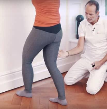 Frau steht mit einem Ausfallschritt an der Wand und dehnt sich die tiefe Wadenmuskulatur gegen Achillessehnenschmerzen