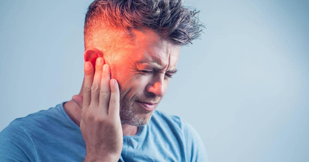Mann greift gequält zum Ohr aufrund eines Tinnitus.