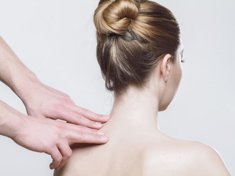 Hände zeigen auf den verspannten Nacken einer Frau. Diese Verspannungen können der Auslöser für Tinnitus sein.