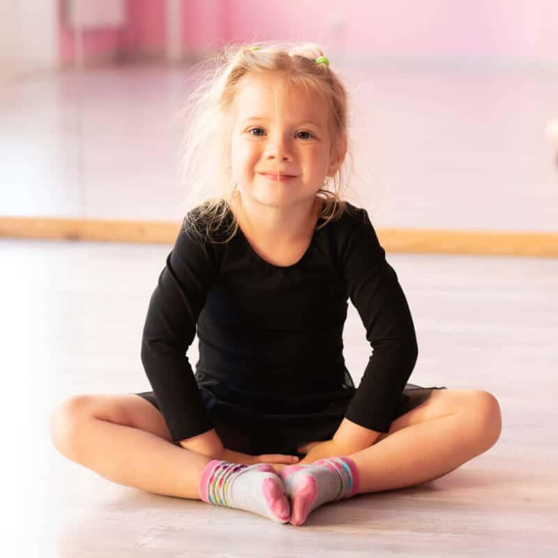 Ein junges blondes Mädchen sitzt gut gelaunt im Schneidersitz in einer Turnhalle