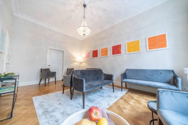 Großes , helles Wartezimmer mit blauen Sitzcouchen und einzelnen Sesseln der Gesundheitspraxis Liebscher & Bracht