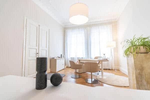 Gesundheitspraxis Liebscher & Bracht - Heller Raum mit hellen Möbeln, wie Tisch, Stühle, Schrank, Lampe und Liege