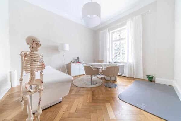 Große, heller Raum in der Gesundheitspraxis von Liebscher & Bracht: Links im vordergrund ein Skelett mit eingezeichneten Punkten vor einer Liege. Rechts daneben Tisch mit drei Stühlen und rechts davon eine Übungsmatte.