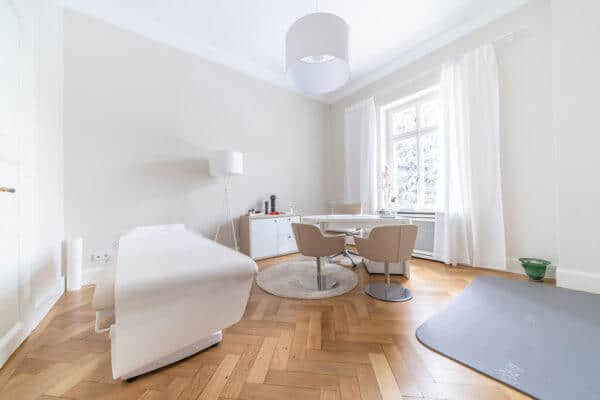 Große, heller Raum in der Gesundheitspraxis von Liebscher & Bracht: Links eine Liege. Rechts daneben Tisch mit drei Stühlen und rechts davon eine Übungsmatte.