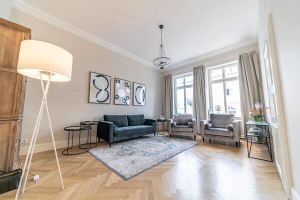 Warteraum in der Gesundheitspraxis Liebscher & Bracht: Großer heller Raum mit Lampe, Bildern an der Wand, einem dunklem Sofa und 2 grauen Sesseln. Es sind Beistelltische daneben.